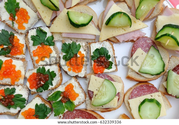 Appetizing sandwiches with caviar, sausage, cucumber and cheese