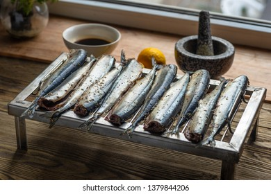 Appetizing saury fish grill for smoking. Smoked saury. Smoked fish with spices