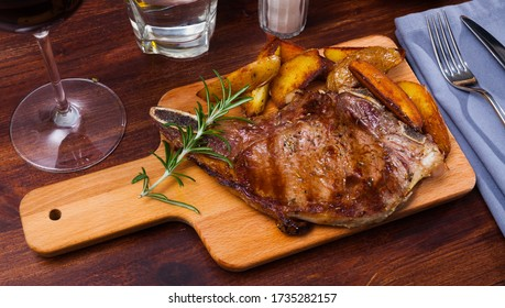 Appetizing savory veal entrecote with fried potatoes on wooden serving board