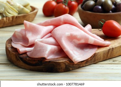 Appetizing set with ham slices on wooden chopping board