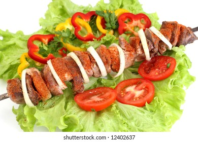 Appetizing shish kebab with tomatoes and greens