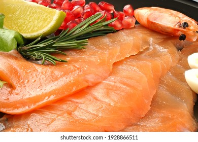 Appetizing slices of sliced salmon with lemon and pomegranate shrimp, delicious food.
