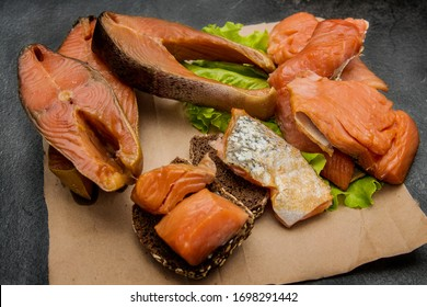 Appetizing smoked fish on the kitchen board. Smoked Mackerel. Smoked fish with spices potion and vegetables.