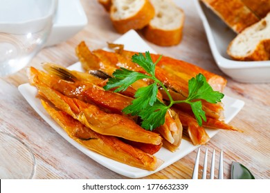Appetizing smoked salmon belly strips with fresh parsley on plate. Popular fish snack