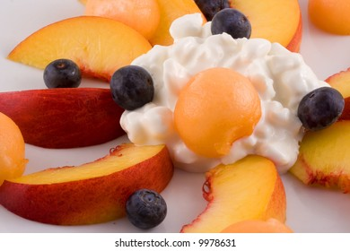 An appetizing snack or breakfast of fresh nectarine, cantaloupe, blueberries and cottage cheese.