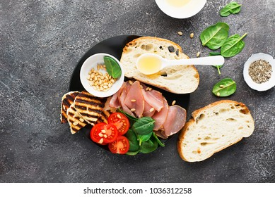 Appetizing snack with fried cheese haloumi, olives, bruschetta, tomatoes, olives, pine nuts, prosciutto, olive oil, honey and spinach Top View