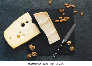 An appetizing solid cheese on a black plate on a gray stone background. Various types of cheese