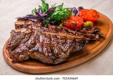 Appetizing steak on the bone, with tomatoes and herbs, on a wooden board
