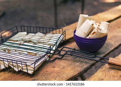 Appetizing Suluguni cheese in pita bread on the barbecue grill and in the cup. Ready for grilling. Table made of wooden planks.