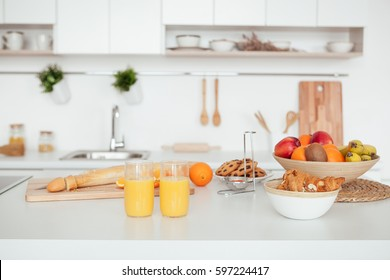 Appetizing Sweet Orange Juice and Two Drinking Glasses standing on a white table in the kitchen for a breackfest. Healthy light meals for breakfast
