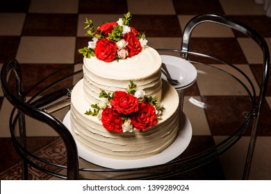 appetizing two-tiered white creamy wedding cake with red and pink roses served on glass tray with plates and spoons