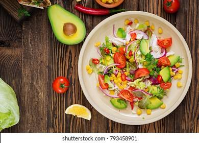 Appetizing vegan salad from tomatoes, avocado, corn, red onion and lettuce leaves.Tasty vegan food. Healthy vegan food. Vegetarian salad.Top view