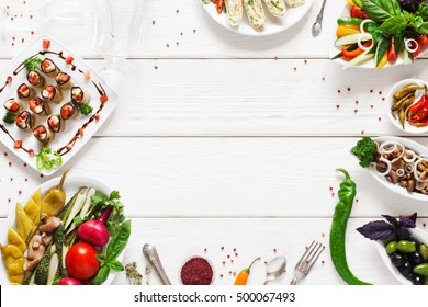 Appetizing vegetarian snacks, free space. Tasty vegetable meals variety on white wooden background with copy space in center. Menu, cuisine, kitchen concept