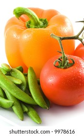An appetizing yellow bell pepper,red tomato and green peas sit on a white surface.