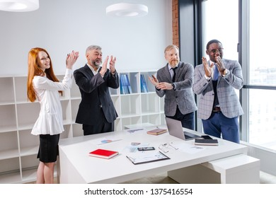 Applauding office workers standing at a Desk in the office. Successful signing of the agreement between different countries
