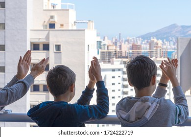 Applause to medical staff. Family clapping hands, applauding from balcony to support doctors, nurses, hospital workers during Coronavirus pandemic quarantine in Spain