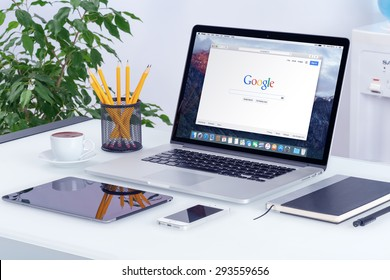 Apple 15 inch MacBook Pro Retina with an open tab in Safari browser which shows Google search web page with iPad and iPhone on the office desk workplace. Varna, Bulgaria - May 29, 2015.