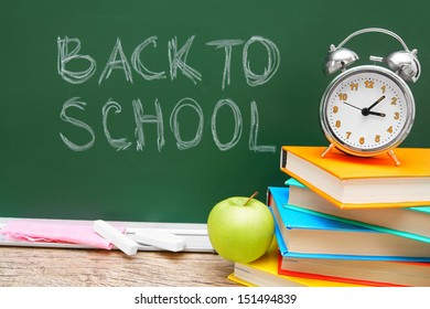 Apple, alarm clock and books against a school board. Back to school.