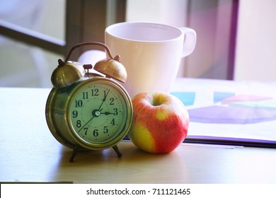 Apple with alarm clock and coffee cup on wooden table