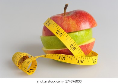 Apple assembled from green and red apple slices wrapped with measure tape on gray background