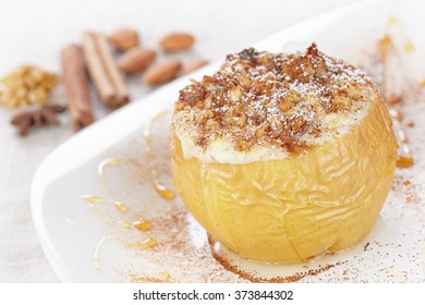 Apple baked with cottage cheese and raisins, decorated with nuts, cinnamon and powdered sugar