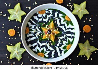Apple, banana, kale, baby spinach, moringa, spirulina and coconut water. smoothie bowl decorated with inca berries, coconut yogurt  and activated charcoal