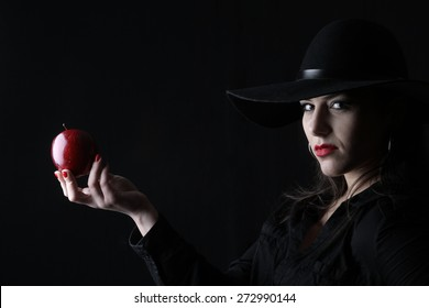 apple - beautiful young brunette woman lady posing in a studio on a black background with old style hat biting a red apple