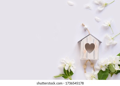 Apple blossom, birdhouse on white background. Flat lay, top view. Spring background