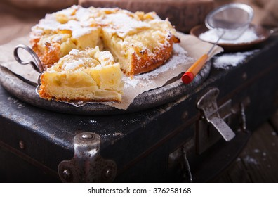 Apple cake on a vintage suitcase in powdered sugar.selective focus.