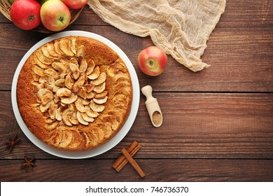 Apple cake in plate on brown wooden table