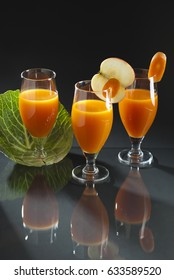 Apple and carrot juice in a glass on the table with reflection