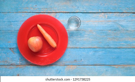 Apple and carrot on a red plate and a glass of water, dieting, healthy nutrition, fitness concept, flat lay, good copy space