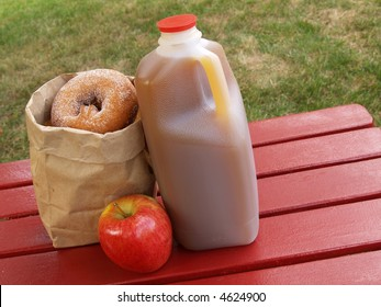 apple cider, an apple and a bag of cinnamon-sugared donuts on a red picnic table