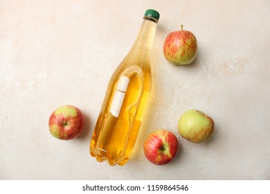 Apple cider in bottle and apples on neutral background. Top view. Concept alcoholic beverage.