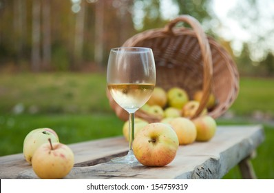 apple cider in a chilled wine glass, rustic settings with apples and wicker basket