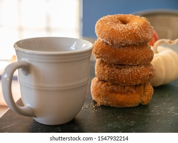 Apple cider donuts with pumpkins and fruit in background and cup of coffee