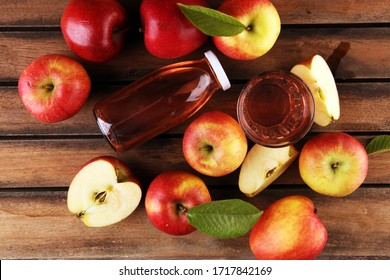 Apple cider drink and apples with leaves on rustic table
