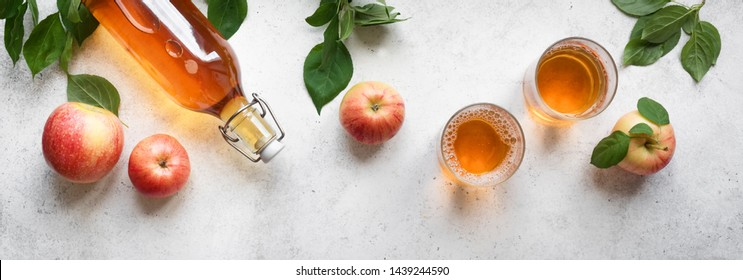 Apple cider drink or fermented fruit drink and organic apples on white, top view, banner. Healthy eating and lifestyle concept.