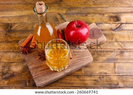 Apple cider in glass bottle with cinnamon sticks and fresh apples on cutting board, on wooden background