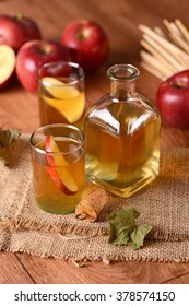 apple cider in glass bottle with fruit around
