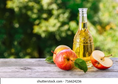 Apple cider, juice or vinegar in glass bottle on wooden table