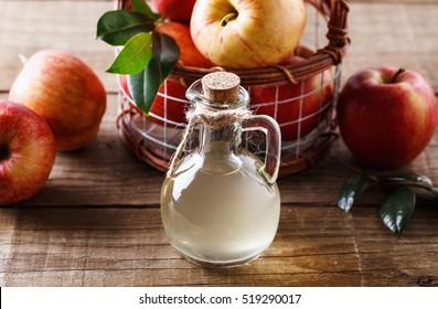 Apple cider vinegar and apples over rustic wooden background close up