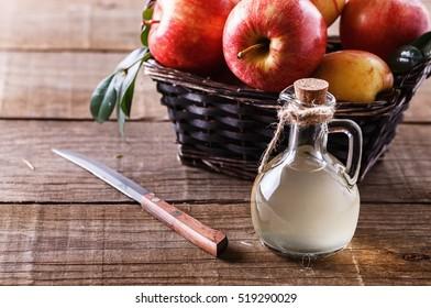 Apple cider vinegar and basket of apples over rustic wooden background