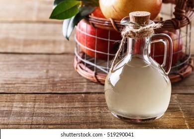 Apple cider vinegar and basket of apples over rustic wooden background close up