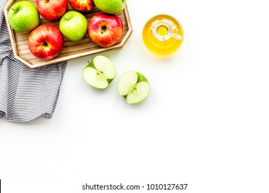 Apple cider vinegar in bottle among fresh apples on white background top view copy space