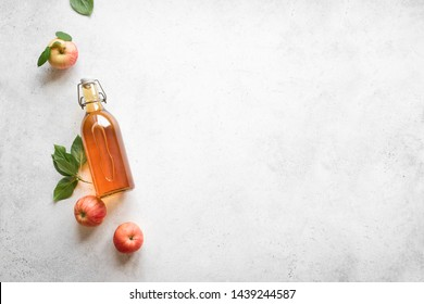Apple cider vinegar or fermented fruit drink and organic apples on white, top view, copy space. Healthy eating and lifestyle concept.