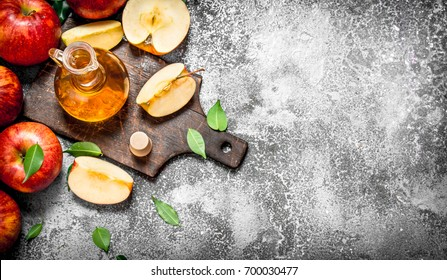 Apple cider vinegar with fresh apples on cutting Board. On rustic background