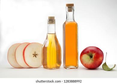 Apple cider vinegar in glass bottle and fresh apples
