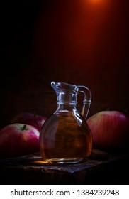 Apple cider vinegar in glass jug, fresh apples, old wooden table, low key, selective focus