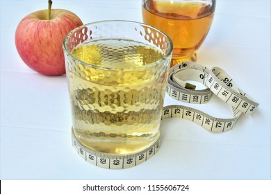 Apple cider vinegar with water in a glass and measuring tape on a table.